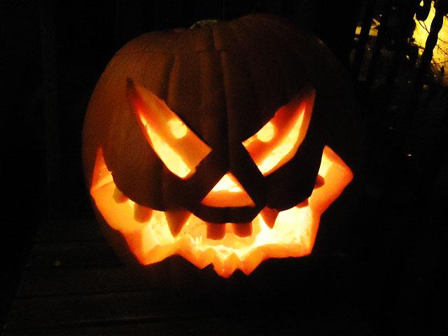 Von innen beleuchteter Halloween-Kürbiskopf im Dunkeln